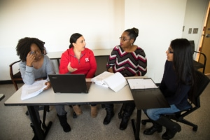 Faculty working with three students