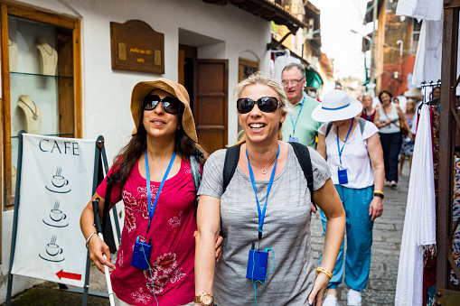 A front-view shot of a multi-ethnic group of tourists walking down a narrow street in Kerala, India. Some of the tourists are visually impaired and can be seen using a blind person's cane and holding onto a friends arm for guidance.