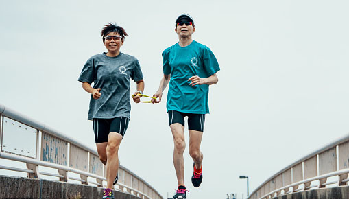 Visually impaired female triathlete running together with her guide