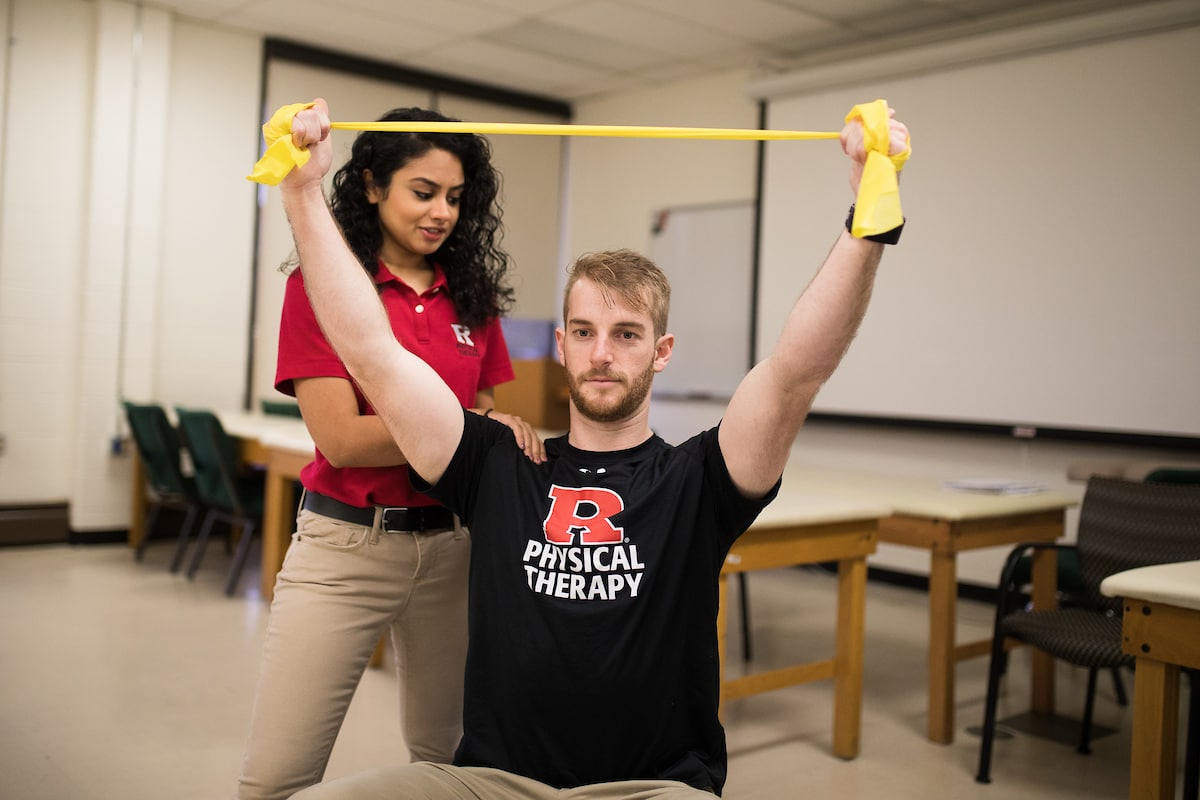 Physical Therapy students demonstrating how to use an arm stretchband