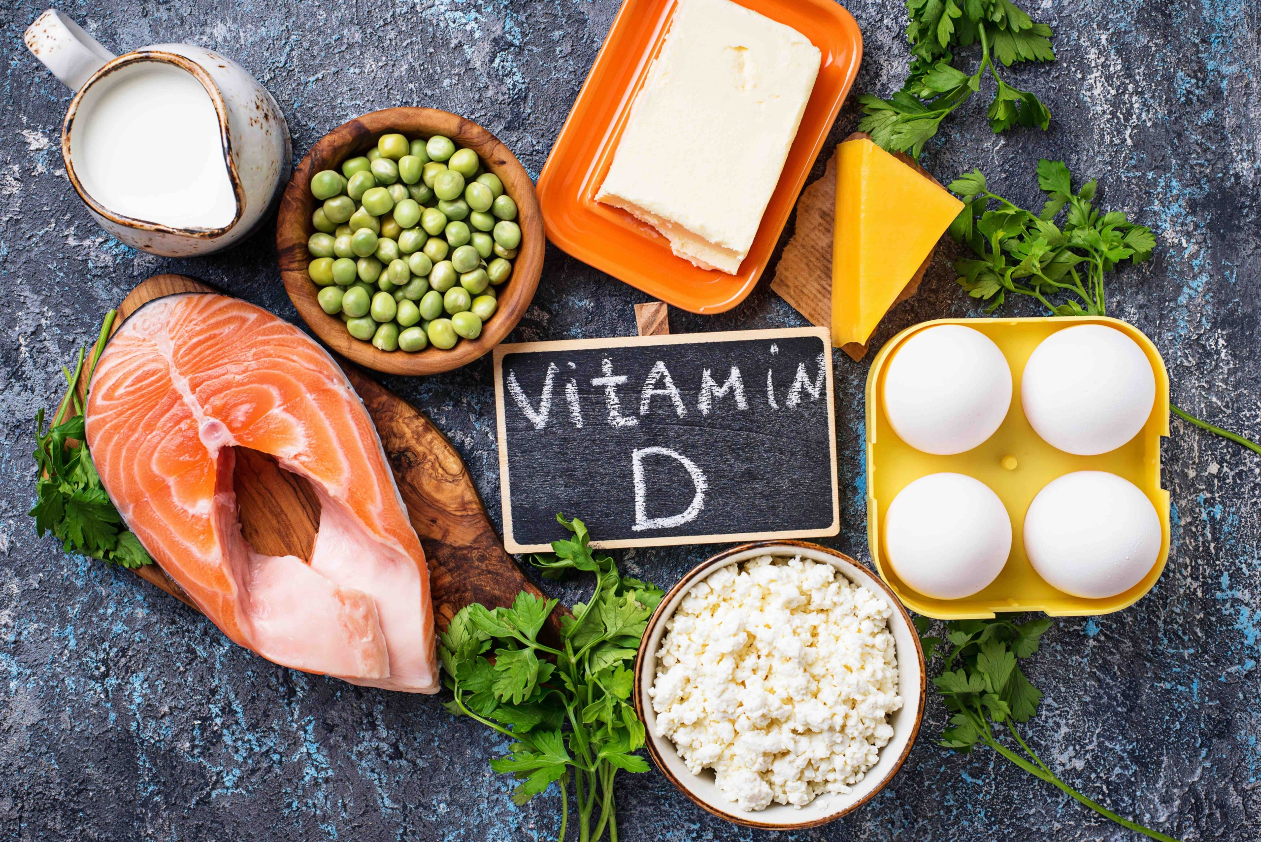 Healthy foods inlucding salmon, peas, cheese, eggs, vitamin D sign