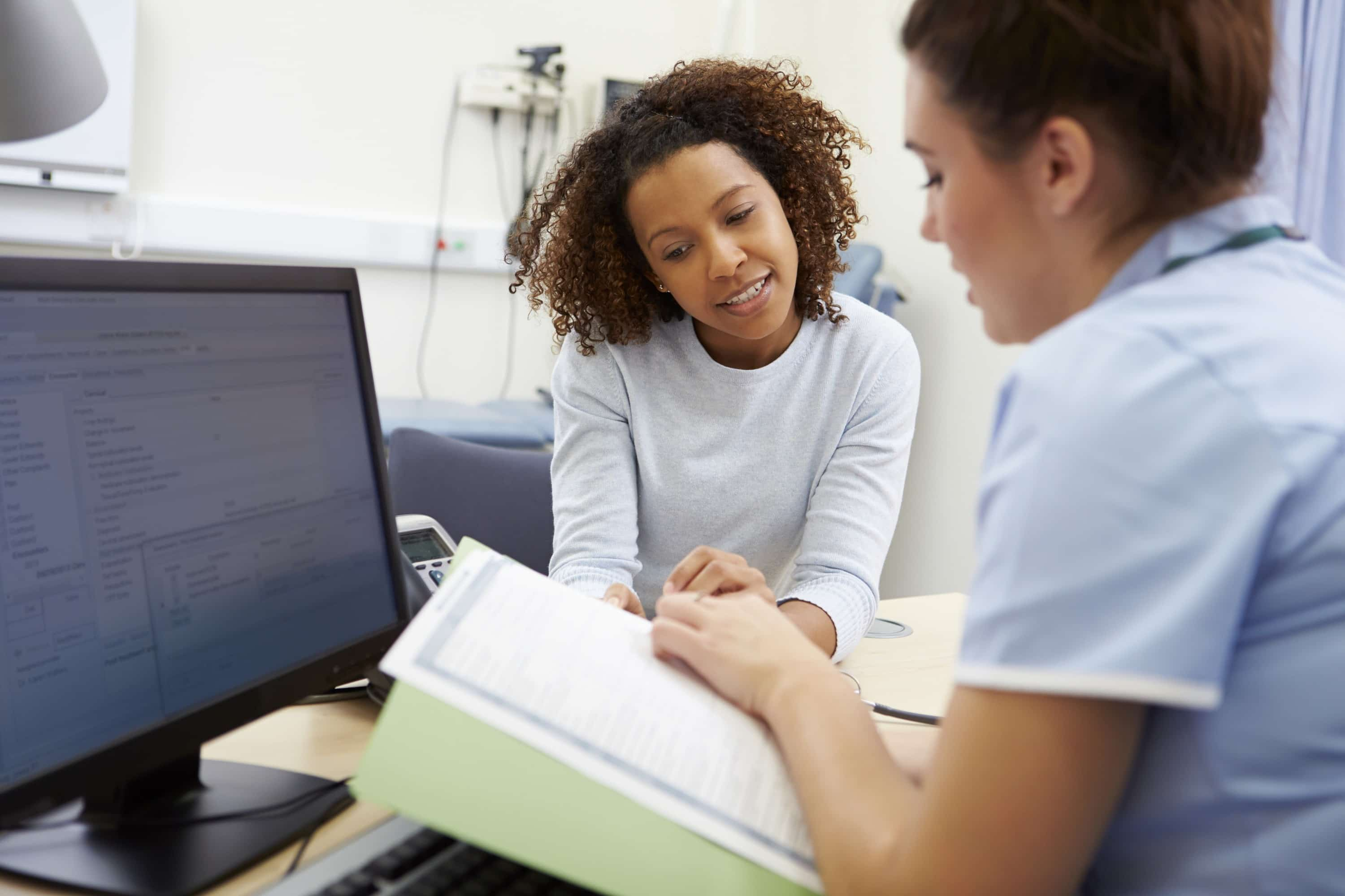 Nurse Discussing Test Results With Patient In Office Looking At Documents