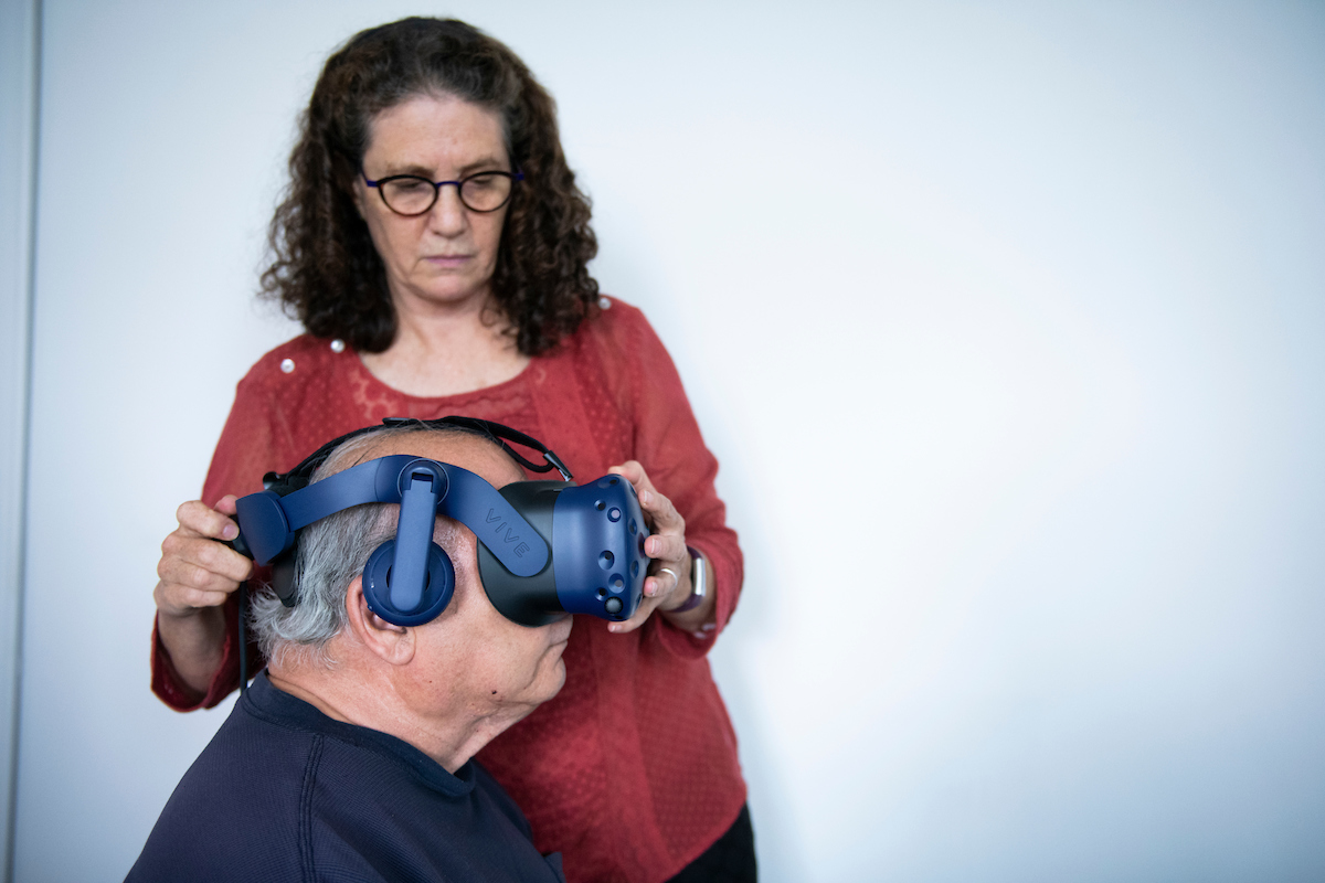 Judith Deutsch adjusts virtual reality goggles on elderly man.